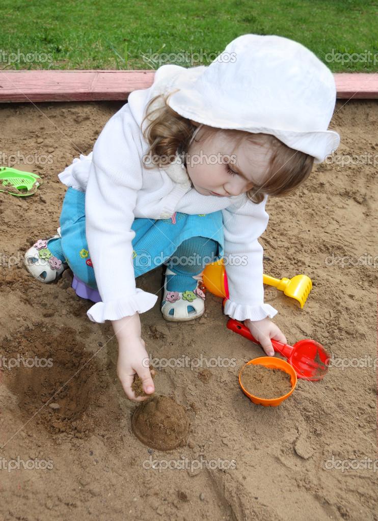 小可爱女孩穿白色巴拿马在沙盒中扮演