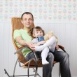 Happy father sits with little daughter in rocking chair at home. — Stock Photo