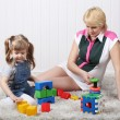 Happy little daughter and her pregnant mother play toys on carpe — Stock Photo