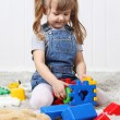 Happy little girl play colorful toys on soft carpet at home. — Stock Photo