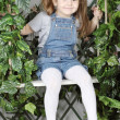 Happy little girl in denim jumpsuit sits on swing under green iv — Stock Photo