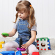 Stock Photo: Happy little girl gathers pyramid among multi-colored toys on so