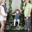 Little girl sits on swing under green ivy and father and pregnan — Stock Photo