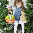 Happy little girl sits on swing under green ivy with teddy bear — Stock Photo