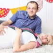 Happy pregnant wife and husband lie on carpet and look at camera — Stock Photo #28613131