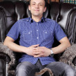 Stock Photo: Young man sits in leather armchair next to shelves with lots of
