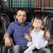Man and her daughter sit in leather armchair next to shelves wit — Stock Photo