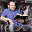 Smiling man sits in leather armchair and reads book next to shel — Foto de Stock