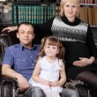Father, mother and daughter sit in leather armchair next to shel — Foto de Stock