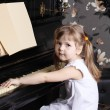 Little beautiful girl in white dress sits at black piano with mu — Stock Photo