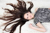 Young girl with long hair wearing striped dress lies on white fu — Stock Photo