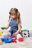 Happy little girl gathers pyramid among multi-colored toys on so — Stock Photo