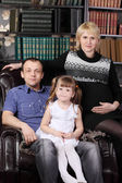 Father, mother and daughter sit in leather armchair next to shel — Stock Photo