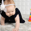 Little baby in dress creeps on grey soft carpet with colorful to — Stock Photo