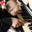 Cute baby sits at knees of her father and plays piano in room. F — Stock Photo #29524311