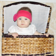Little beautiful baby sits in big wicker basket and peeps out in — Stock Photo