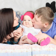 Young father, beautiful mother kiss cute baby and lie on bed at  — Stock Photo