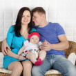 Happy father, beautiful mother and baby sit on wicker sofa at ho — Stockfoto