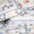 Stock Photo: Beautiful and soft colored pillows lie on double bed with blanke