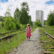 Little cute girl in pink dress walks at railway at sunny summer — Stock Photo