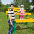 Stock Photo: Happy little cute girl with her father at playground at summer d