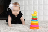 Little cute baby in dress creeps on grey soft carpet among toys. — Stock Photo