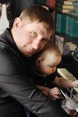 Roztomilé dítě sedí na kolenou jejího otce a klavír v místnosti se dotýká. — Stock fotografie