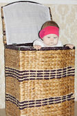 Little cute baby sits in big wicker basket and peeps out in room — Stock Photo