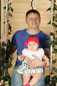 Happy father with cute baby sits on swing overgrown with green i — Stock Photo