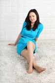 Happy young woman in blue dress sits on soft carpet and looks at — Stock Photo