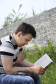 Young brunet man in jeans intently reads book outdoor at summer — Stock Photo