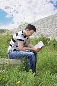 Young man in jeans intently reads book outdoor at summer day. — Stock Photo