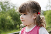 Little cute girl in pink dress thinks and looks away at summer d — Stock Photo