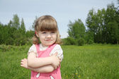 Little cute girl looks away at small field at sunny summer day o — Stock Photo