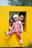 Happy little girl with father sits in window of yellow box at pl — Stock Photo