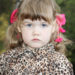 Serious little girl with pink bows in overcoat looks at cameri — Stock Photo #29745107