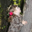 Pretty little girl with pink bows in overcoat keeps tree and loo — Stock Photo #29745443