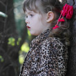 Pretty little girl with pink bows in overcoat looks away in fore — Stock Photo #29746093