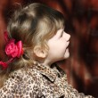 Pretty little girl with pink bows in overcoat looks up at sunny — Stock Photo #29747651