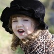 Stock Photo: Beautiful little girl in black hat shouts outdoor at autumn day.