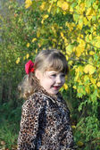 Smiling little girl looks away next to yellow trees in park at s — Stockfoto