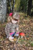 Całkiem mała dziewczynka z różowym łuki w płaszcz siedzi następnego ropucha czerwona — Zdjęcie stockowe