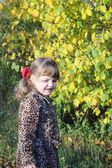 Happy little girl smiles next to yellow trees in park at sunny a — Stock Photo