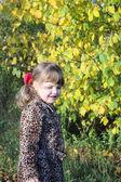 Glückliche kleine mädchen lächelt neben gelb bäume im park am sonnigen ein — Stockfoto