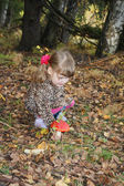 Pretty little girl with bows in overcoat disrupts red toadstool — Stock Photo