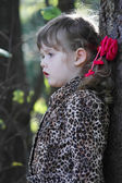 Pretty little girl with pink bows in overcoat looks away in fore — Stock Photo