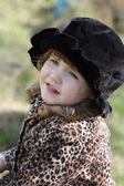 Beautiful happy little girl in black hat looks away outdoor at a — Stock Photo