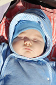 Little cute baby in blue jumper sleeps in buggy at sunny day. — Stock Photo