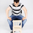 Brunet handsome man sits on chair and looks small wooden chair o — Stock Photo