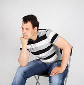 Brunet man in striped T-shirt sits on chair and thinks on grey b — Stock Photo